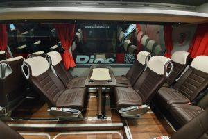 Vista interior Mercedes Tourismo con mesas y asientos enfrentados. Sólo previa petición expresa y según disponibilidad.